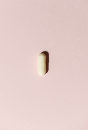 One white pill on orange background. Minimalist concept for medicine.