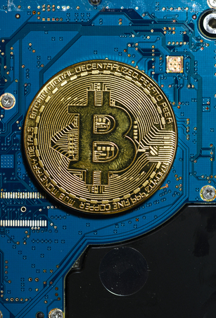 Bitcoin coin on blue circuit board. Cryptocurrency concept. Technology and finance background.