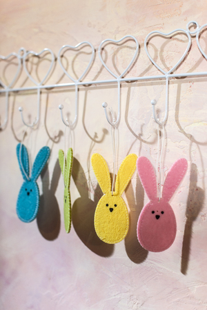 Easter bunny hooked on the wall in a room. Multi Colored easter rabbits made of fabric on pink wall. Hard light from window and shadows on the wall. White vintage hanger. Stock Photo