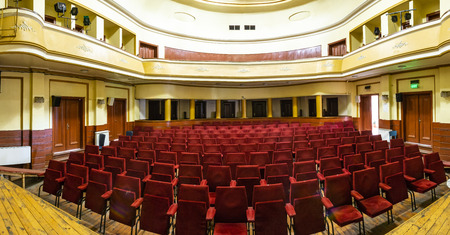 Theater interior. Yellow curtain. Red seats in theater interior. Vintage classic scene. Art performance. Concept for visual arts. Two floors with lodges for the audience. Yellow walls.