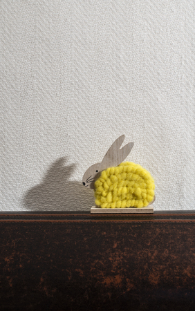 Yellow easter bunny in front of white wall in a room. Bunny decoration and white wallpaper background. Shadow of rabbit on the wall. Wooden bunny figure shape and yellow yarn. Minimalist concept. Imagens