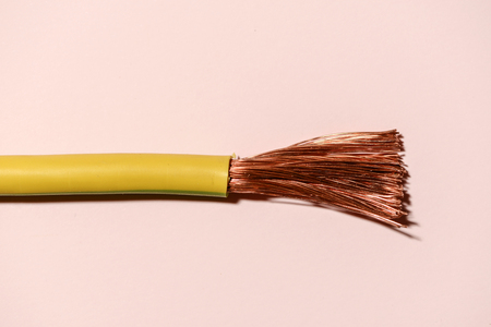 Electrical cable on pink pastel background. Spread out copper wires. Minimalist electrical background.