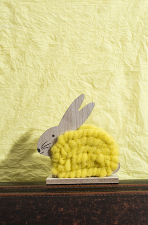 Yellow easter bunny in front of yellow paper wall. Bunny decoration. Shadow of rabbit on the wall. Wooden bunny figure shape and yellow yarn. Minimalist concept.
