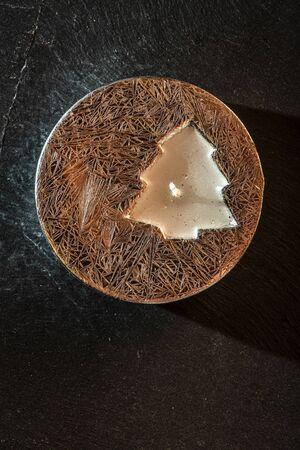 Christmas candle on tree shape. Flame of candle inside christmas tree. Shiny circle on dark stone background.