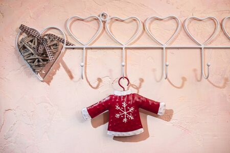 Red Santa Clause sweater with snowflake hooked on pink wall. White hanger with heart shapes. Love christmas concept. Copy space.