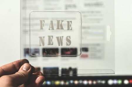 Fake news text and website on the background. Fake news conception with transparent words. Blurred Images and articles on background.