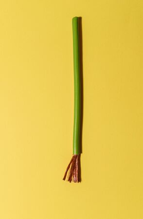 Electrical cable on yellow background. Spread out copper wires. Minimalist electrical background. Imagens