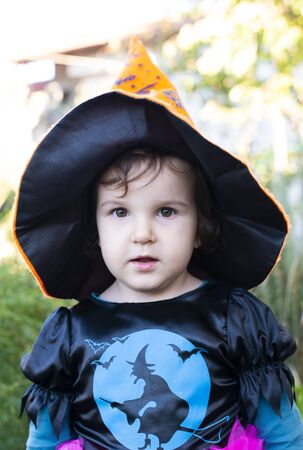 A little girl with a Halloween costume. Black witch hat on head.