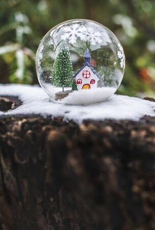 Transparent cristalball with christmas tree and house inside. Snow in christmas ball. Stock Photo