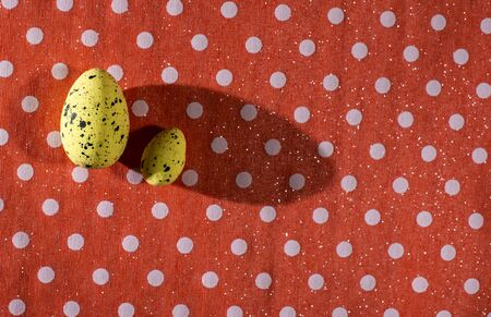 Yellow easter eggs decoration on red background on dots. Long shadows. Imagens