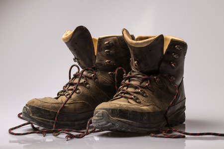undone: Pair of worn brown leather hiking boots with undone laces viewed low angle over a grey background Stock Photo