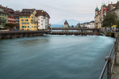 townhouses: Waterfront view of Lucerne, Switzerland at dusk with colorful historic townhouses overlooking an old bridge and weir on Lake Lucerne Editorial
