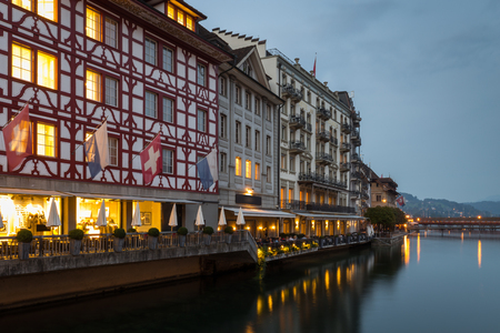 Tranquil night scene with reflections of the lights in the calm water of Lake Lucerne of the historic timbered buildings on Lucerne waterfront, Switzerland in a scenic view