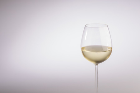 oenology: Half filled stylish long stemmed glass of white wine in a close up partial view over a grey background with copy space in a concept of wine, wine making and viticulture Stock Photo