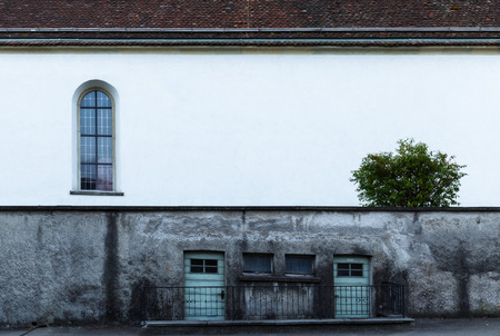 guarded: Grungy exterior wall of an urban building with three old doors guarded by metal railings and an arched window in the white upper section with copy space Stock Photo