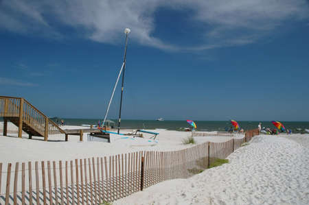 shrimp boat: Beach scene with beach umbrellas, chairs, sailboat, and shrimp boat.