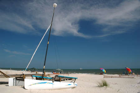 shrimp boat: Beach scene with beach chairs, umbrellas, sailboat, and shrimp boat.