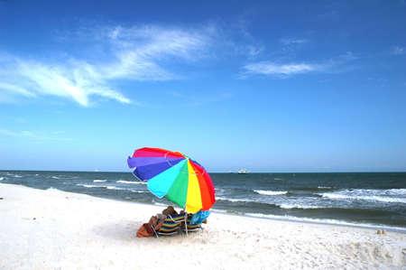 水にエビのボートと傘とビーチチェアのビーチのシーン。