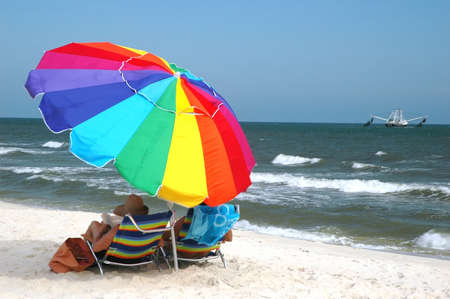 Beach scene with beach chairs and umbrella with shrimp boat in water.