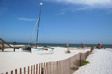 shrimp boat: Beach scene with beach chairs, umbrellas, sailboat, wooden fence, and shrimp boat in water.