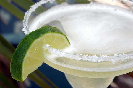 Margarita with salt and lime with palm tree in background. photo