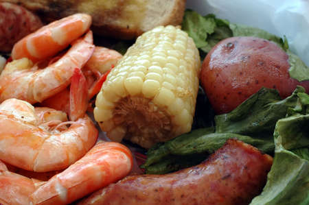 Shrimp boil with corn on the cob, sausage, potatoes, and bread. photo