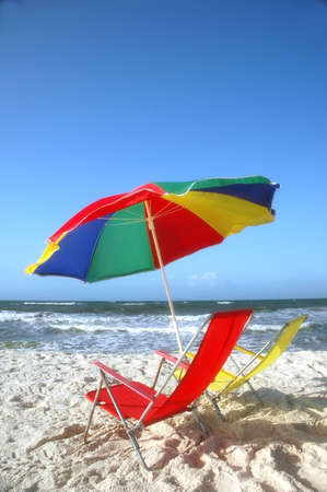 Morning at the beach with beach chairs and umbrella.