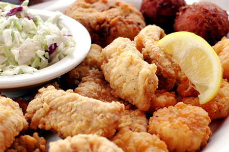 Fried seafood platter with fish, crab cakes, oysters, shrimp, hush puppies, cole slaw, and lemon slice.