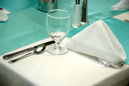 Corner of table with formal setting in restaurant.