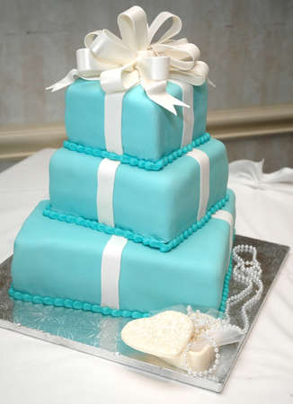 Formal birthday cake on table with necklace and heart-shaped box