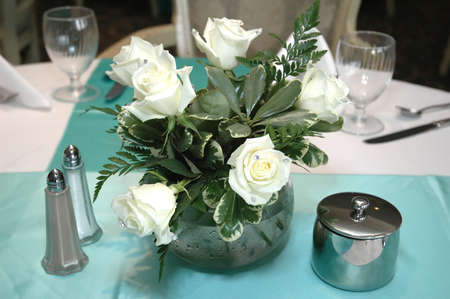White roses centerpiece on formal dining table.