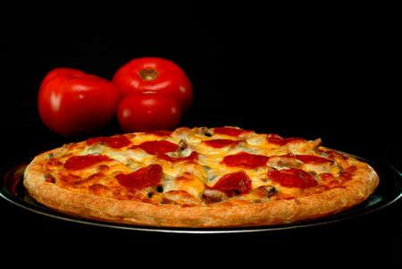 バック グラウンドでトマトと全体のペパローニ入りピザ。 黒の背景に分離しました。