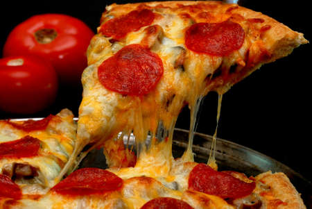 Slice of pepperoni pizza being removed from whole pizza with tomatoes in background.  Isolated on black background.