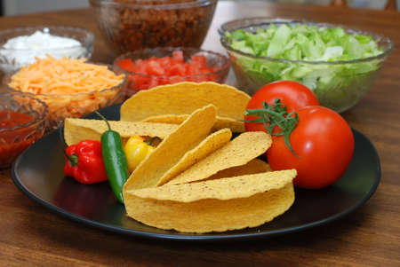 ingredient: Taco shells, tomatoes, habanero and serrano peppers with taco ingredients in background.