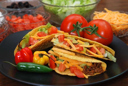 Prepared tacos with tomatoes, habanero and serrano peppers on plate.  Ingredients in background.