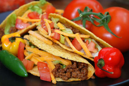 Closeup of tacos on plate with tomatoes, habanero and serrano peppers. 写真素材