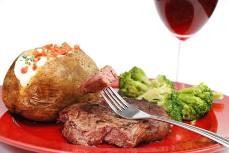 Grilled rib eye steak with baked potato and broccoli.  Isolated on white background. photo