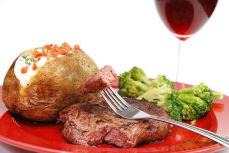 ribeye: Grilled rib eye steak with baked potato and broccoli.  Isolated on white background. Stock Photo