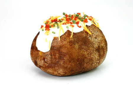 Baked potato loaded with butter, sour cream, cheddar cheese, bacon bits, and chives.  Isolated on white background.