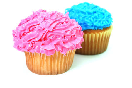 frosting: Pink and blue cupcakes with decorative frosting.  Isolated on white background.