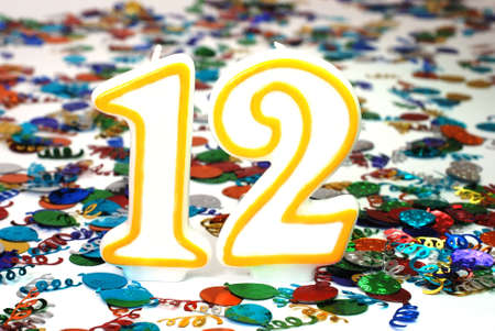 number 12: Number 12 celebration candle with confetti. Stock Photo