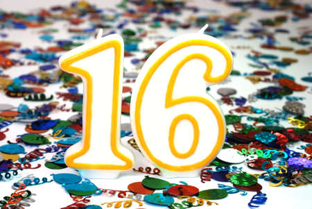 Number 16 celebration candle with confetti.