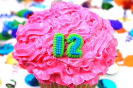 number 12: Number 12 celebration cupcake with confetti. Stock Photo