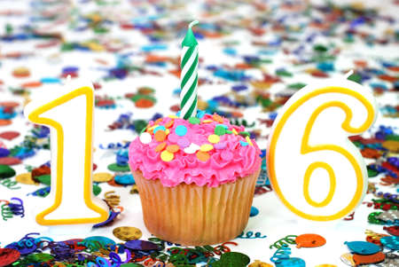 sweet sixteen: Number 16 celebration cupcake with candle and sprinkles with confetti in background.