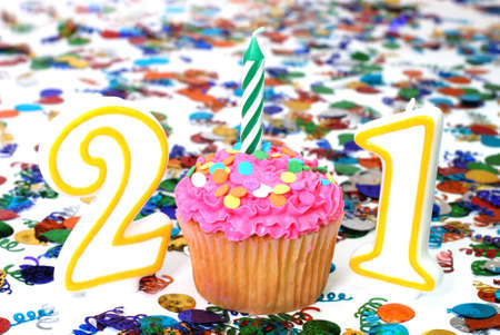 21: Number 21 celebration cupcake with candle and sprinkles.  Confetti in background. Stock Photo