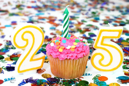 20 25: Number 25 celebration cupcake with candle and sprinkles.  Confetti in background.