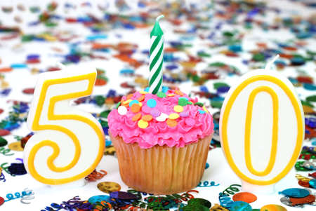 number 50: Number 50 celebration cupcake with candle and sprinkles.  Confetti in background. Stock Photo