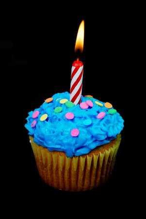 candle: Celebration cupcake with lit candle on black background. Stock Photo