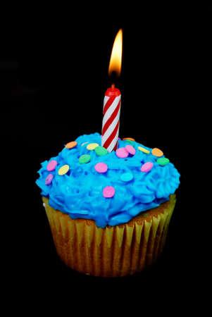 Celebration cupcake with lit candle on black background. Stock Photo - 2835933