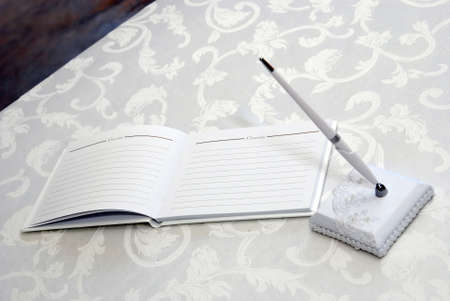 Guest book and pen on table at wedding.